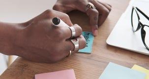 Homme d'affaires écrivant l'emploi du temps de la réunion sur la note adhésive banque de vidéos