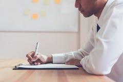 Homme d'affaires écrivant la forme pour soumettre pour reprendre l'employeur pour passer en revue la demande d'emploi photo libre de droits