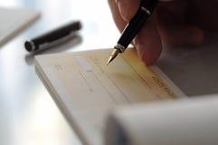 Homme d'affaires écrivant le chèque Photographie stock libre de droits