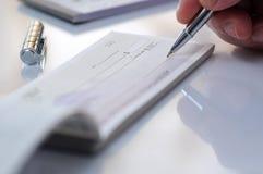 Homme d'affaires écrivant le chèque Image stock