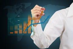 Homme d'affaires écrivant une croissance d'affaires sur un graphique sur le scre virtuel Photographie stock libre de droits