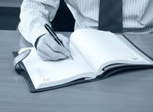 Homme d'affaires écrivant une note Image stock