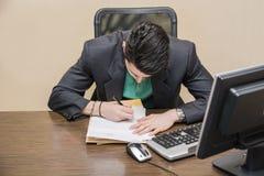Homme d'affaires élégant s'asseyant à son fonctionnement de bureau Photos libres de droits