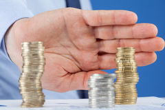 Homme d'affaires éloignant la colonne d'euro pièces de monnaie Image stock