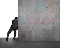Homme d'affaires éloignant le mur en béton de griffonnages Photo stock