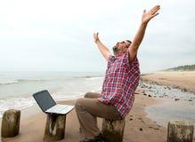 Homme d'affaires émotif avec l'ordinateur portable sur la plage Photo stock