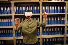 Homme d'affaires éprouvant la réalité virtuelle dans la chambre de stockage de fichier photo libre de droits