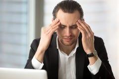 Homme d'affaires épuisé ayant un mal de tête après de longues heures de travail Photos stock