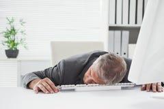 Homme d'affaires épuisé dormant à son bureau image stock