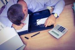 Homme d'affaires épuisé dormant sur le bureau Photo stock
