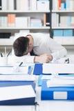 Homme d'affaires épuisé dormant sur son bureau Image stock