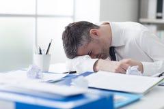 Homme d'affaires épuisé dormant sur son bureau Images libres de droits