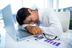Homme d'affaires épuisé dormant sur son ordinateur portable images stock