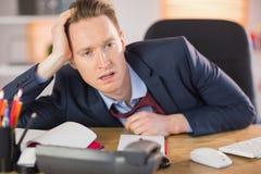 Homme d'affaires épuisé travaillant à son bureau photo libre de droits