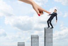 Homme d'affaires équilibrant sur la colonne concrète verticale avec une main femelle géante se dirigeant à lui Photographie stock libre de droits