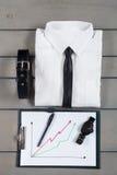 Homme d'affaires, équipement de travail sur le fond en bois gris Chemise blanche avec le lien noir, ceinture, planchette De nouve Images stock