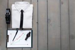 Homme d'affaires, équipement de travail sur le fond en bois gris Chemise blanche avec le lien noir, ceinture, planchette De nouve Photos stock