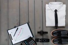 Homme d'affaires, équipement de travail sur le fond en bois gris Chemise blanche avec le lien noir, montre, ceinture, chaussures  Images stock