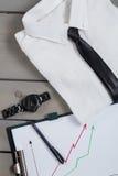 Homme d'affaires, équipement de travail sur le fond en bois gris Chemise blanche avec le lien noir, montre, ceinture, chaussures  Photo stock