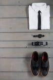 Homme d'affaires, équipement de travail sur le fond en bois gris Chemise blanche avec le lien noir, montre, ceinture, chaussures  Image libre de droits