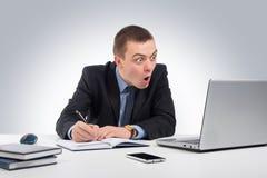 Homme d'affaires étonné avec l'ordinateur portable et documents à l'offi Photographie stock libre de droits