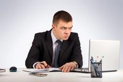 Homme d'affaires étonné avec l'ordinateur portable et documents au bureau sur le fond gris Photographie stock libre de droits