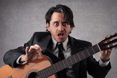 Homme d'affaires étonné tirant la ficelle d'une guitare Photos libres de droits