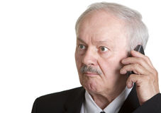 Homme d'affaires aîné au téléphone semblant étonné Images stock