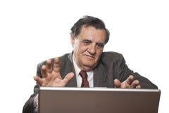 Homme d'affaires aîné avec faire des gestes d'ordinateur portatif Images stock
