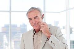 Homme d'affaires aîné avec l'écouteur en fonction Photos libres de droits