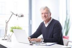 Homme d'affaires aîné avec l'ordinateur portatif Images stock
