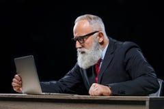 Homme d'affaires aîné avec l'ordinateur portatif Image libre de droits