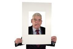 Homme d'affaires aîné avec le support de photo effectuant des visages Photo libre de droits