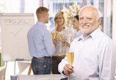Homme d'affaires aîné célébrant dans le bureau Photographie stock libre de droits