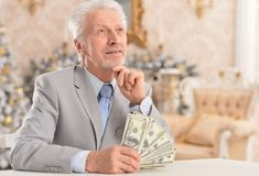 Homme d'affaires aîné comptant l'argent Photos stock