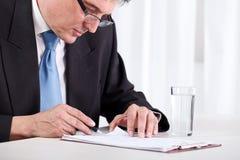 Homme d'affaires aîné contrôlant le contrat Photographie stock