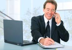Homme d'affaires aîné heureux travaillant dans le bureau Image stock