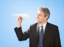 Homme d'affaires aîné projetant un avion de papier Image stock