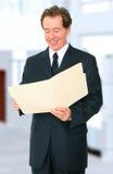 Homme d'affaires aîné recherchant le dépliant Photos libres de droits