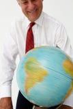 Homme d'affaires aîné regardant et tournant un globe Images libres de droits