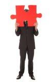 Homme d'affaires aîné retenant un puzzle denteux Images libres de droits