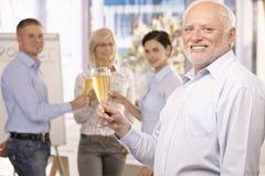 Homme d'affaires aîné soulevant la glace de champagne Photos libres de droits