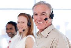 Homme d'affaires aîné travaillant à un centre d'attention téléphonique Image libre de droits