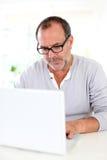 Homme d'affaires aîné travaillant sur l'ordinateur portatif Images stock