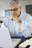 Homme d'affaires aîné travaillant sur l'ordinateur portatif Image libre de droits