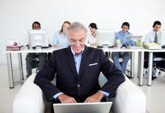 Homme d'affaires aîné utilisant un ordinateur portatif Images libres de droits