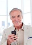 Homme d'affaires aîné utilisant un téléphone portable Image libre de droits