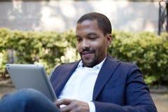 Homme d'affaires africain américain de sourire dans des vêtements informels fonctionnant à la rue ensoleillée sur le pavé tactile Photos libres de droits