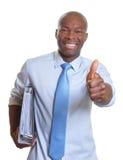 Homme d'affaires africain avec des documents montrant le pouce Photographie stock libre de droits