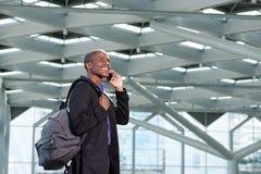 Homme d'affaires africain de déplacement marchant avec le téléphone portable et le sac Images libres de droits